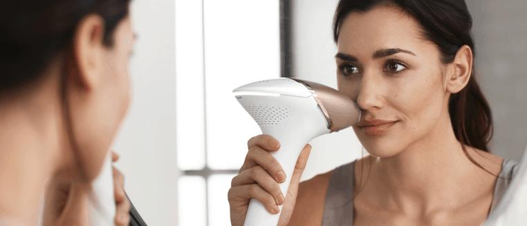 mujer usando una depiladora IPL en la cara
