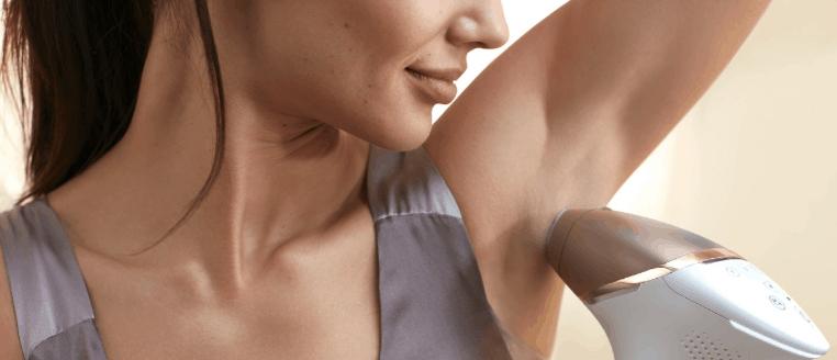 mujer usando una depiladora IPL en la axila