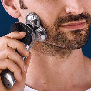 hombre usando maquina afeitar philips