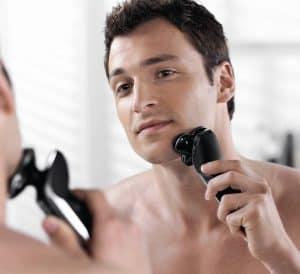 hombre usando una máquina de afeitar rotativa
