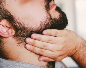 hombre poniendo aceite para la barba en la barba