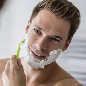 hombre usando espuma de afeitar con cuchilla