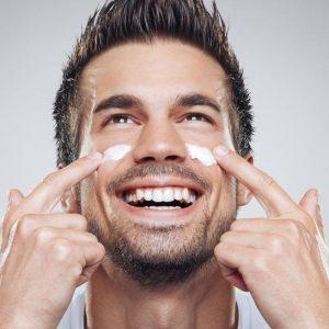 hombre poniéndose crema en la cara