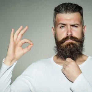 hombre con barba larga que usa aceite para la barba