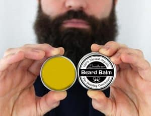 hombre sujetando bálsamo para la barba