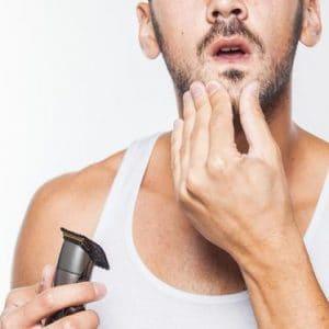 hombre con máquina de afeitar eléctrica