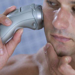 hombre usando una máquina de afeitar eléctrica