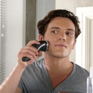 joven afeitándose con una máquina de afeitar eléctrica