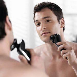 hombre usando máquina de afeitar eléctrica moderna