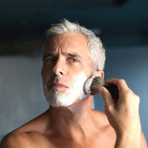 hombre usando una brocha de afeitar