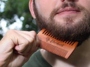 hombre usando un peine para la barba de madera