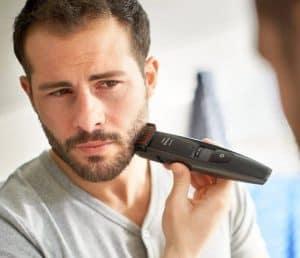 joven perfilándose la barba con un barbero