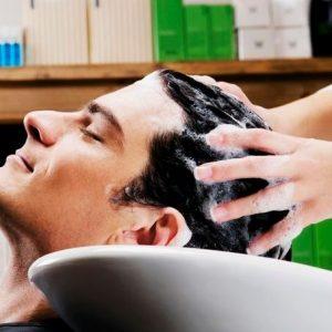 hombre con caspa lavándose el pelo
