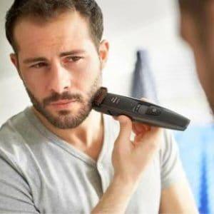hombre joven usando una recortadora de barba philips