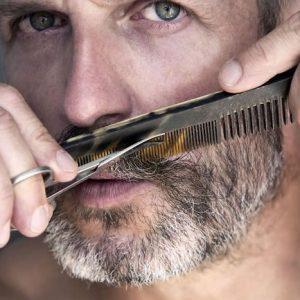 hombre usando un peine para cortarse la barba