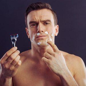 hombre joven usando productos para después del afeitado