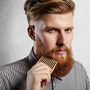 hombre pelirrojo peinándose la barba