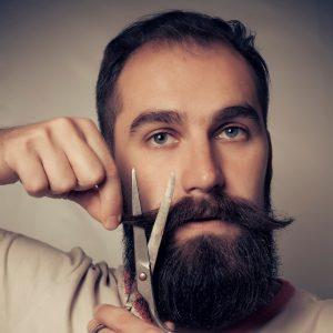 hombre cortandose el bigote con tijeras