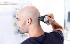 hombre usando una cortapelos para raparse el pelo