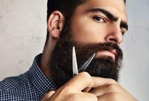 hombre recortándoselas la barba con tijeras