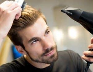 chico joven usando un secador de pelo