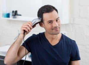 hombre usando cortapelos multifunción con cable