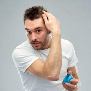 hombre aplicándose cera para el pelo