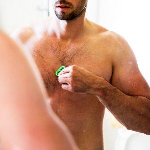 hombre depilándose el pecho con una cuchilla bajo el agua