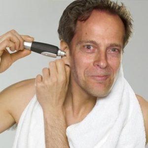 hombre usando un recortador de nariz y orejas en la oreja