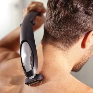 hombre usando una afeitadora corporal en la espalda