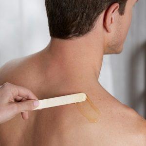 hombre depilándose la espalda con cera