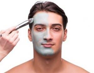 hombre con exfoliante facial en media cara