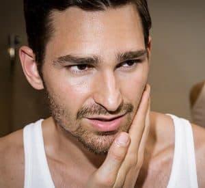 hombre poniéndose crema facial hidratante