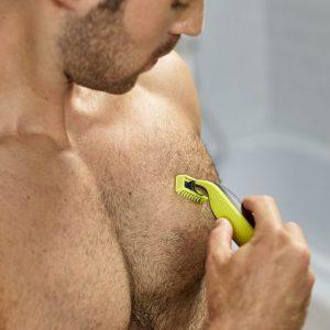 hombre rasurándose el pecho con una afeitadora corporal