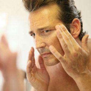 hombre aplicándose exfoliante facial