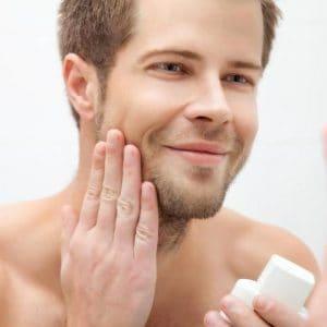 joven poniéndose crema facial antiarrugas para hombre