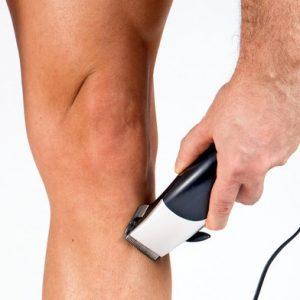 hombre recortándoselas los pelos de la pierna con maquinilla
