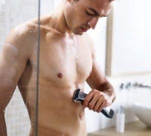hombre usando una afeitadora corporal bajo la ducha
