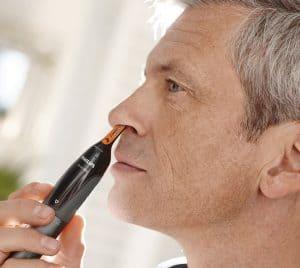 hombre usando una recortadoras para nariz y orejas
