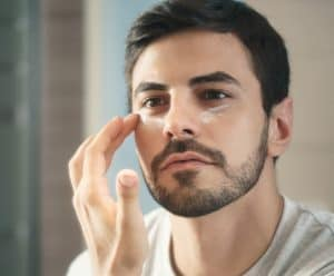 hombre joven con crema facial antiarrugas
