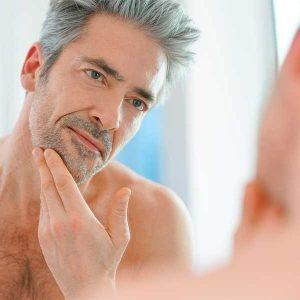 adulto poniéndose crema facial antiarrugas para hombre