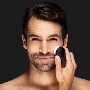 hombre usando un cepillo limpiador facial