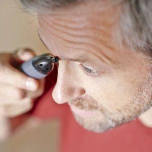 hombre usando recortadora para nariz y orejas en las cejas
