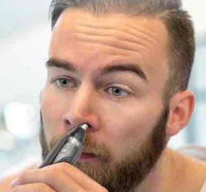 hombre joven usando un recortador de nariz y orejas