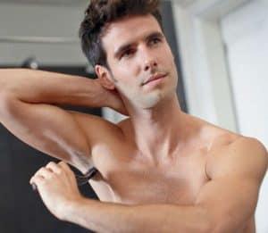 hombre usando una afeitadora corporal en la axila