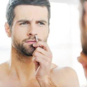 hombre depilándose los pelos de la nariz