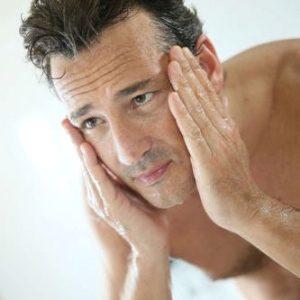 hombre lavándose la cara