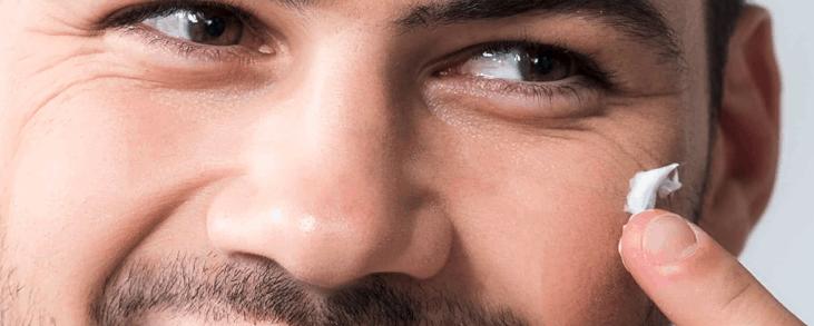 hombre sonriendo con crema facial hidratante