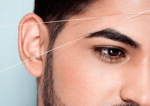 hombre depilándose las cejas con hilo