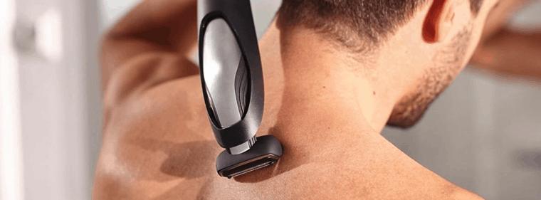 hombre usando afeitadora corporal en la espalda